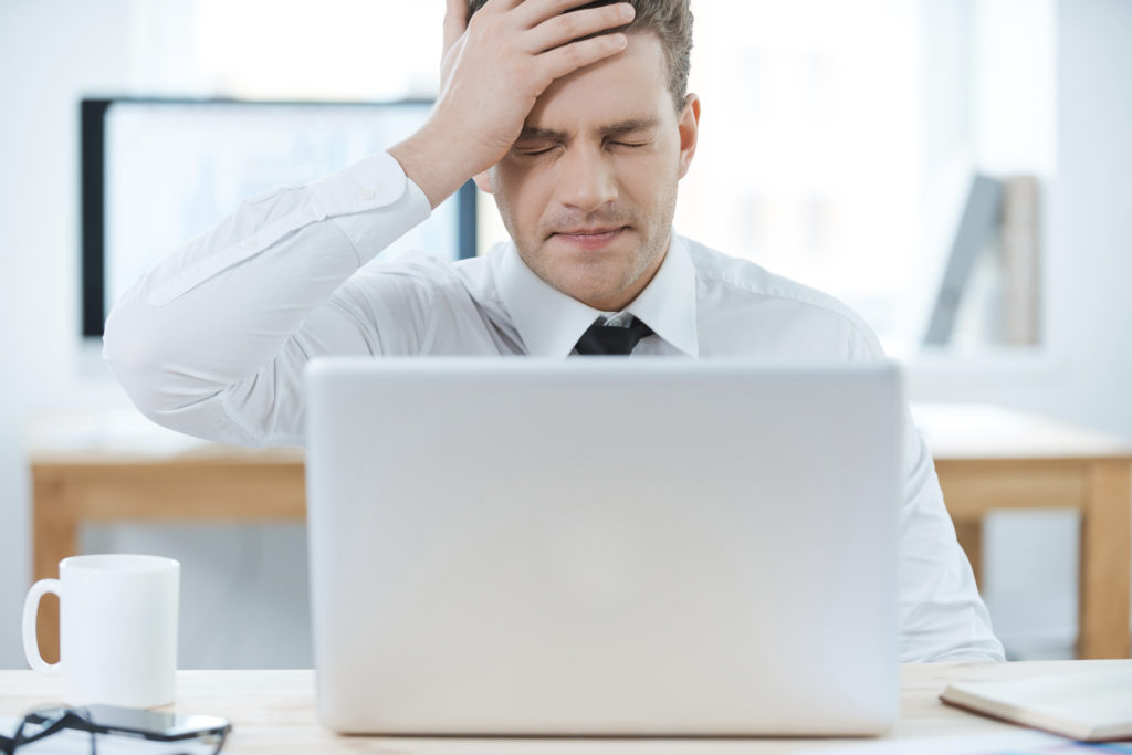 Oh no! Frustrated businessman working on laptop and touching his head while sitting at his working place