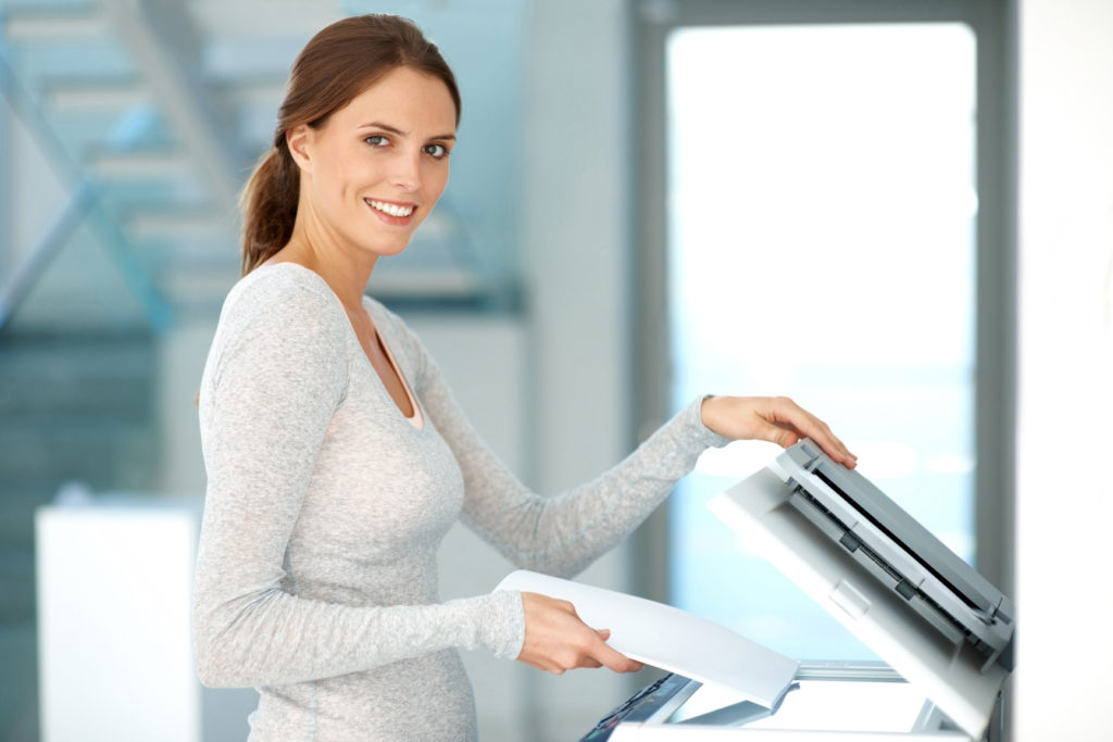 Pretty young businesswoman making copies on the photocopy machine  at the office